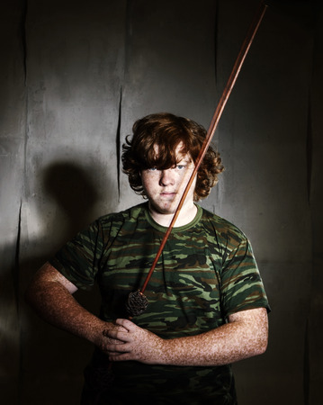 Red-haired freckled fat boy posing like a soldier, studio shooting