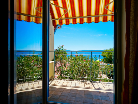 louver: Beautiful view to sea from the inside of apartments. Balcony with marquee. Croatia, sunny day.
