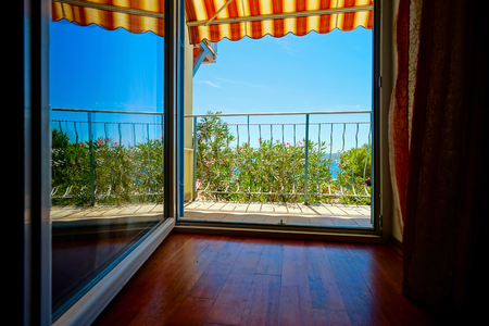 Beautiful view to sea from the inside of apartments. Balcony with marquee. Croatia, sunny day.