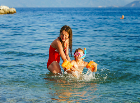 Two sisters playing games and swimming in the sea, Adriatic, Croatia Stock Photo