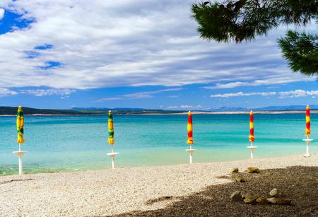 Leeg overzees strand met gesloten zon-paraplu's, Kroatië, stormachtig weer, de zomer Stockfoto