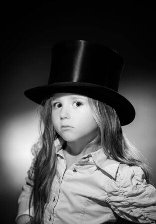 Cute little girl posing in gibus, old-style opera hat, vintage photo