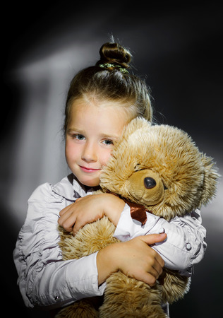 Cute little girl posing with her teddy-bear toy, retro style