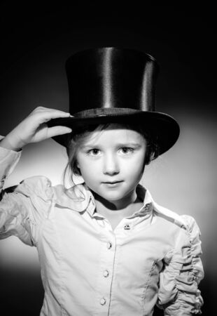 oldstyle: Cute little girl posing in gibus, old-style opera hat, vintage photo