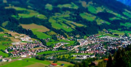 tilt views: Tilt-shift aerial view of little austrian city in the valley, Austria, summer Stock Photo