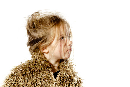 Disheveled preschooler girl with long hair dressed in fur coat, isolated on white background