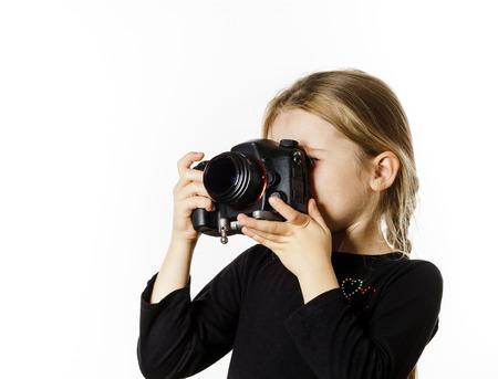 Meisje dat beelden neemt door professionele digitale camera, die op witte achtergrond wordt geïsoleerd Stockfoto