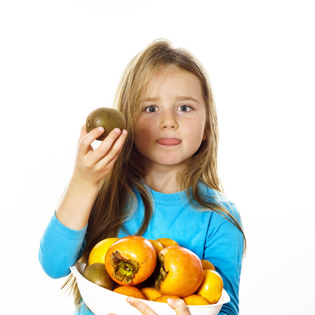 Cute little girl with plate of fruits: kiwi, date plum, mandarins, etc., isolated on white background Stock Photo