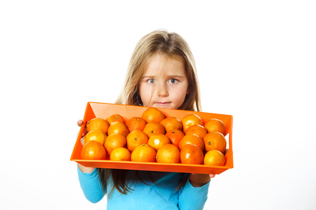 Cute little girl with full tray of mandarins, isolated on white background
