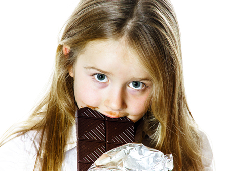 Cute little girl eating tablet of chocolate, isolated on white background