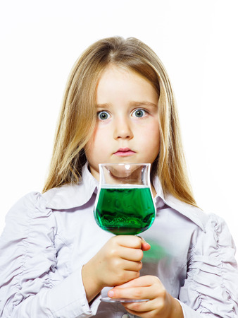 maybe: Little girl with glass of vivid green liquid, maybe poison, isolated on white background Stock Photo