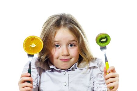 Funny little girl selecting between kiwi and orange, isolated on white background