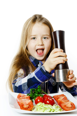 Cute little girl with salad and pepper box, isolated on white background Stock Photo