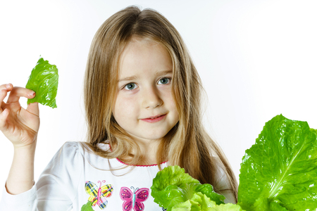 Cute little girl posing with fresh salad leaves, isolated on white background