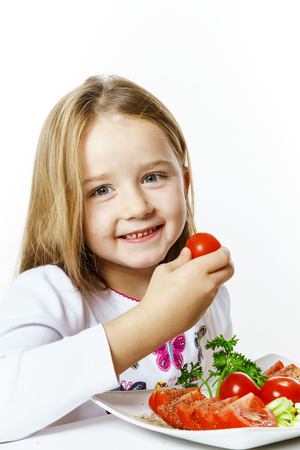 Cute little girl with plate of fresh vegetables, isolated on white background