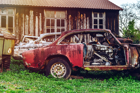 Abandoned old rusty body and parts of retro car, outdoor