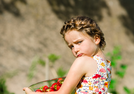 Cute little girl posing with fresh red strawberry in the sunny garden, hairdress bunches style