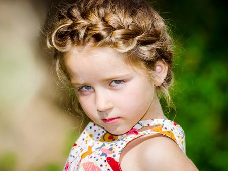Cute little preschooler girl natural portrait on the sun, hairdress bunches style, children fashion Stock Photo