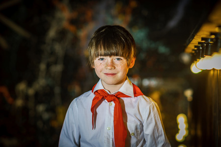 Redhead attractive boy dressed like soviet pioneer with red tie, studio