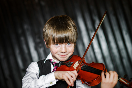 Attractive boy playing violin, studio shooting, music concept
