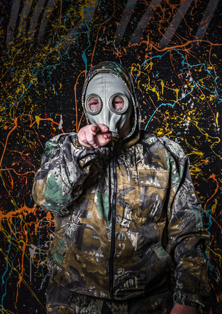 tun: Man dressed into military wear and gas mask, ecology and toxic concept, studio light Stock Photo