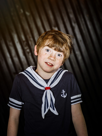 Schoolboy posing in sailor costume with emotions, studio shooting