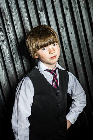 Little serious boy posing in official suit, studio