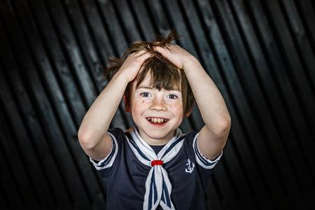 Schoolboy posing in sailor costume with emotions, studio shooting