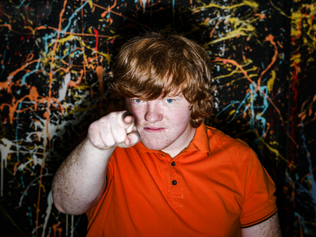 Red-haired freckled fat boy showing to youwith serious face