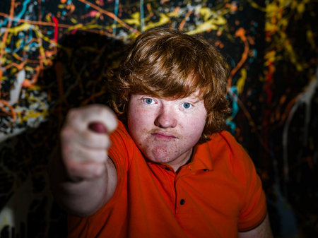 Red-haired funny fat boy showing fig sign