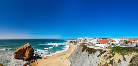 Yellow rocks and sand on portuguese coastline, vivid ocean water, panoramic view