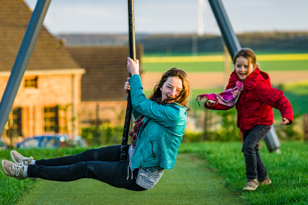 Two sisters: preschooler and teenage - playing on playground, sunny evening photo