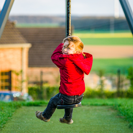 Cute little girl playing on children playground, sunset time Stock Photo