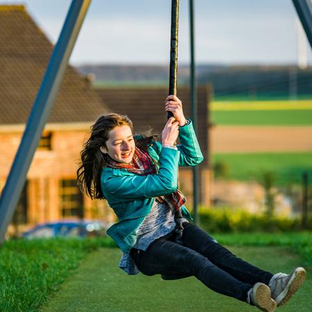 Teenage girl playing on children playground, sunny evening Stock Photo