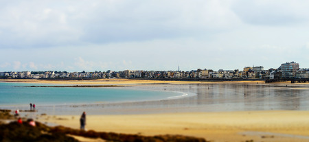 Yellow sandy beach miniature tilt-shift view while low tide water, Brittany, France