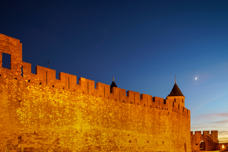 Carcassonne medieval fortress highlighted night view with moon in blue sky, France Reklamní fotografie