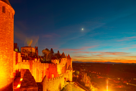 Carcassonne medieval fortress highlighted night view with moon in blue sky, France 写真素材