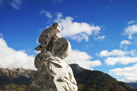 Stoned sculpture of cyclist on blue sky background. Tour de France trace, top point in Spain. Sport concept