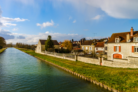 Green water of canal and blue sky, springtime in countryside, France Stock Photo