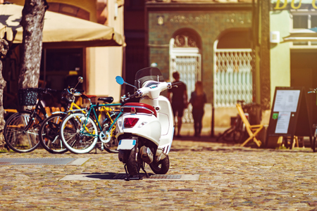 Sunny holidays in old city, Vespa scooter on the street, Strasbourg