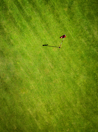 Green golf field with flag aerial view from drone, France