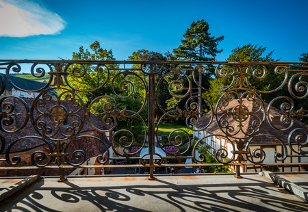 Wrought iron fence on old balcony, shadows of the sun, summer