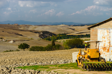 Tractor on the field, Tuscany, autumnal plowing, agricultural concept, Italy Imagens