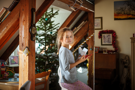 Cute little daughter portrait in the morning with sunlight through the windows, indoor
