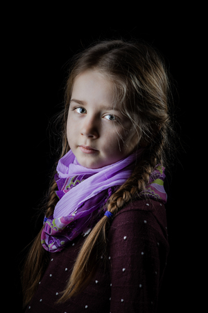 Beautiful little girl portrait on black background, seriously child, indoor Stock Photo