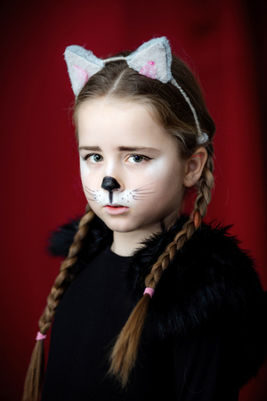 Cute little girl dressed and maked-up like a cat, childhood Stock Photo