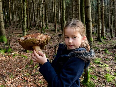 Little girl demonstrates a white mushroom just found in the forest, Alsace