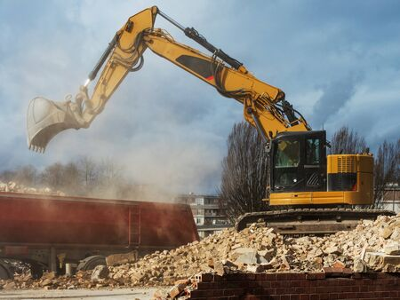 An excavator breaks down an old building. Dust, bricks and broken walls. Construction.