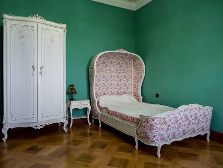 Classic Italian-style children's room interior, plush bed and wardrobe. green colored walls Stock Photo