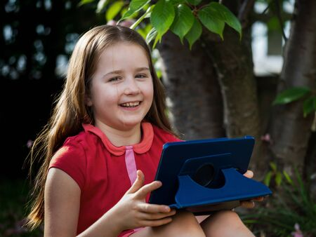 Distance learning during the quarantine period for the virus Covid-19. Cute little schoolgirl with long hair is studying from home, sitting in the garden on the grass. Uses a tablet and remote work via the Internet.
